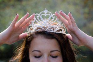 Das Bild zeigt eine junge Frau, die sich ein Diadem aufsetzt als Symbolbild für das Königin Sein über ein begrenztes Areal | Minimalismus