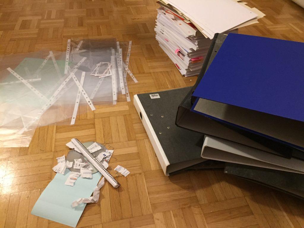 Das Bild zeigt einen Stapel Unterlagen, Dokumentenhüllen und Stehordner auf dem Fußboden, was alles minimalisiert wurde   Kristina Kral, Minimalismus