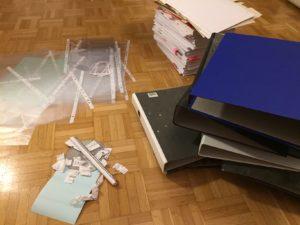 Das Bild zeigt einen Stapel Unterlagen, Dokumentenhüllen und Stehordner auf dem Fußboden, was alles minimalisiert wurde | Kristina Kral, Minimalismus