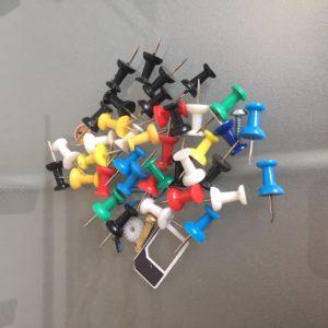 Das Bild zeigt ein Häufchen aus Kleinkram aus einer meiner Schachteln: Reißzwecken, Schrauben, ein Simkartenadapter, ein Plastikteilchen, eine Büroklammer | Kristina Kral, Minimalismus