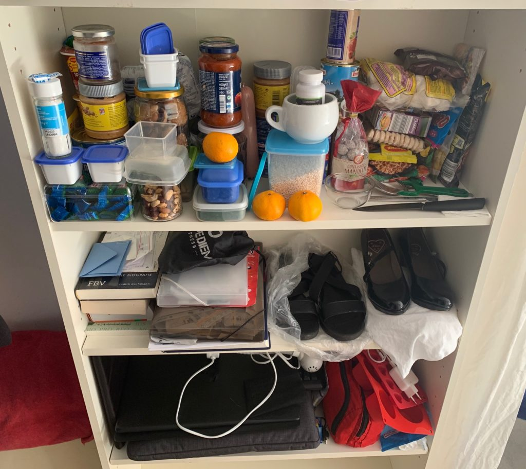 Das Bild zeigt die untere Regalhälfte: im dritten Fach sind Küchenutensilien und Lebensmittel, im vierten Fach sind zwei Paar Schuhe, Bücher und Schreibutensilien, im fünften Fach sind Laptop, Zubehör, Werkzeug und das sechste Fach ist leer