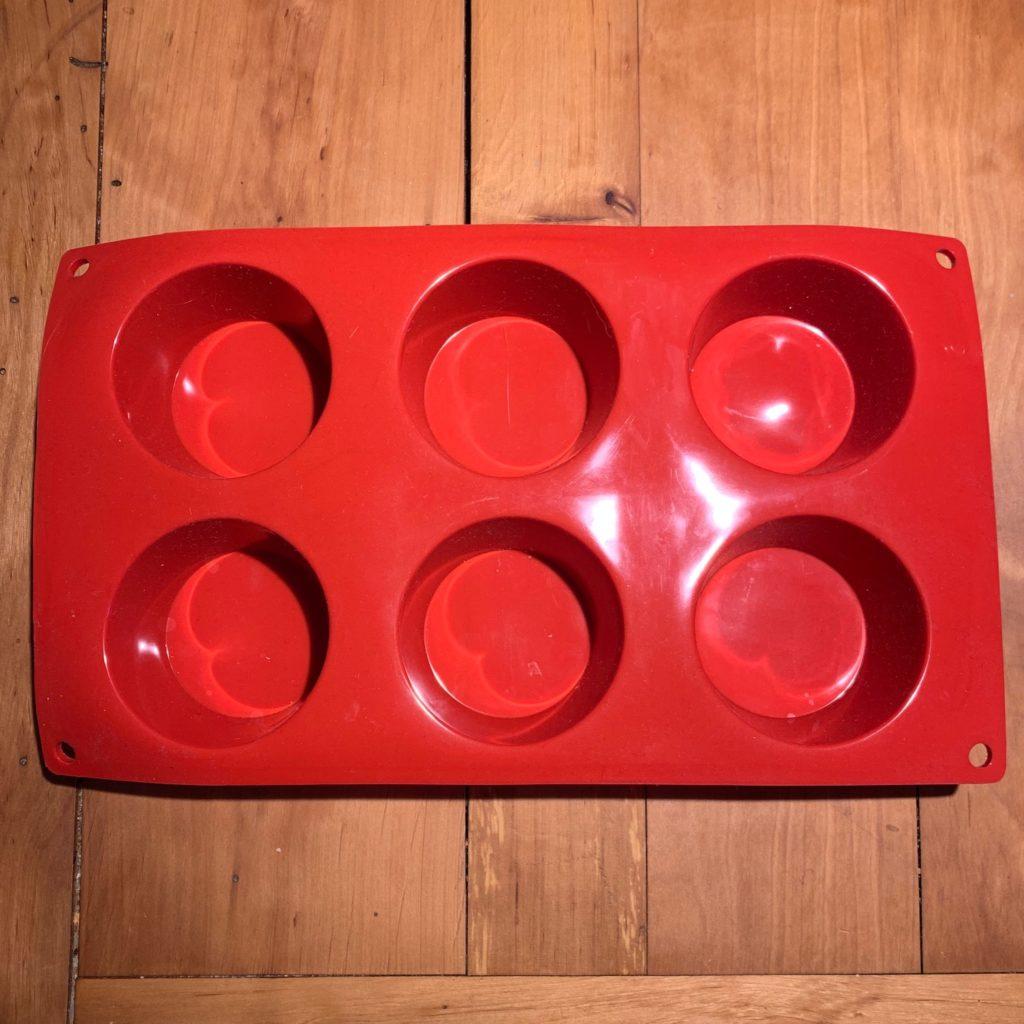 Das Bild zeigt eine rote Silikonbackform für sechs Muffins