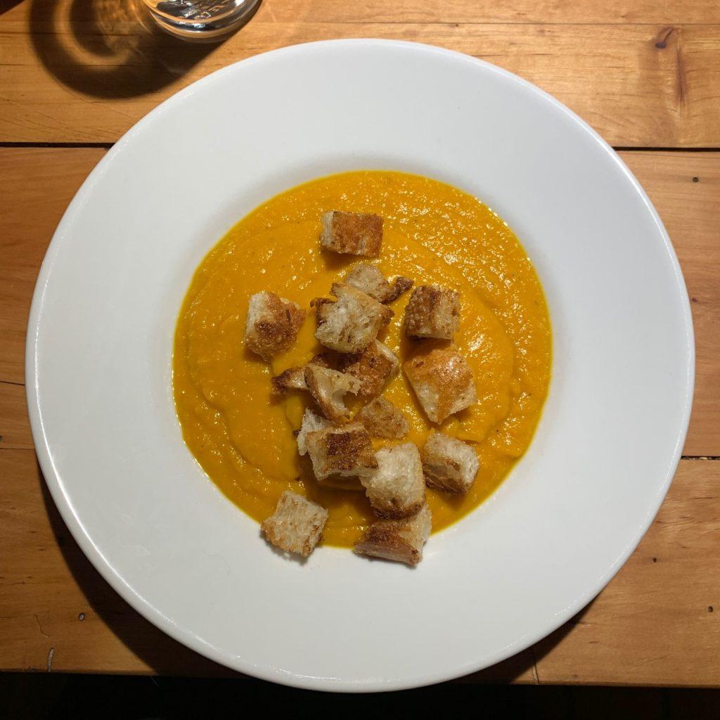 Das Bild zeigt einen Suppenteller mit Kürbissuppe mit Brotwürfeln