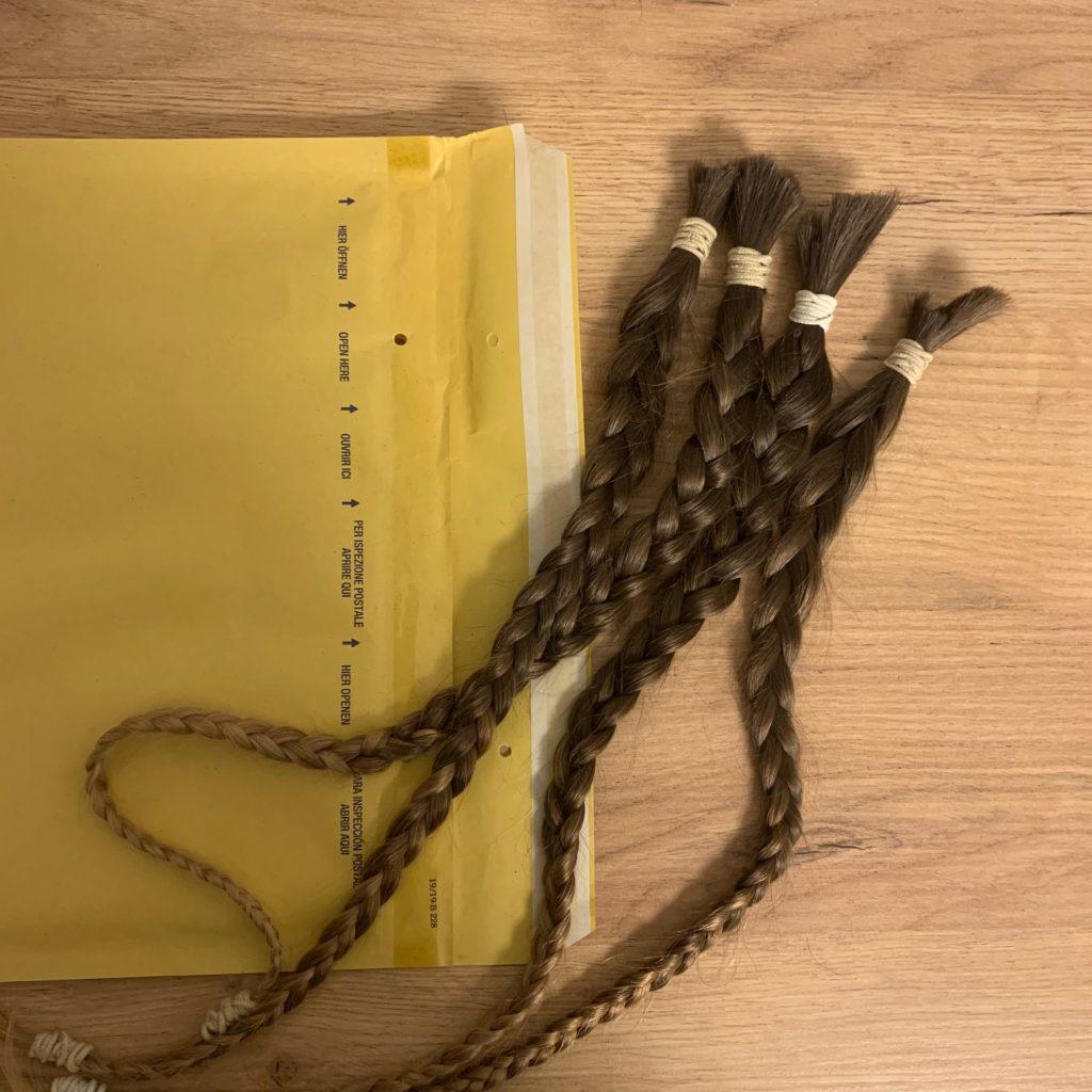 Das Bild zeigt einen Briefumschlag und eine Haarspende