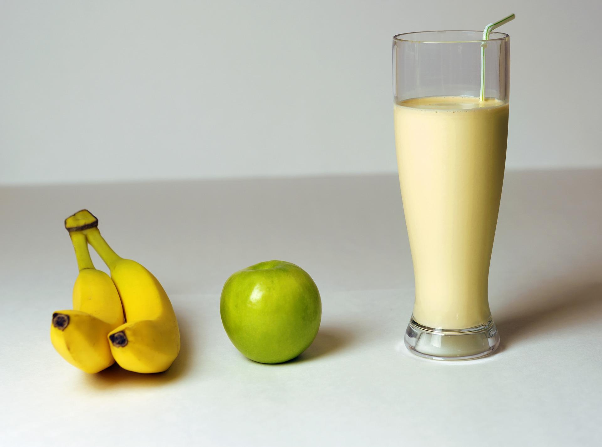 Das Bild zeigt zwei Bananen neben einem Apfel und einem großen Glas Bananen-Apfel-Smoothie // Kristina Kral (c) ImagesBG via pixabay.com