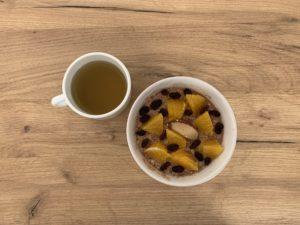 Das Bild zeigt Mahlzeit 1: eine Schüssel mit Müsli und eine Tasse Tee