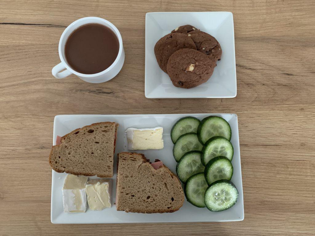 Das Bild zeigt Mahlzeit drei: Kakaogetränk, Kekse, Brot, Brie, Gurke