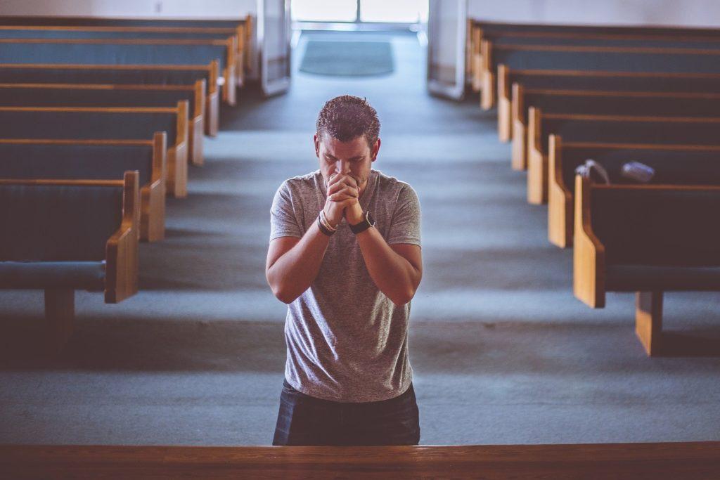 Das Bild zeigt einen betenden Mann in einer Kirche