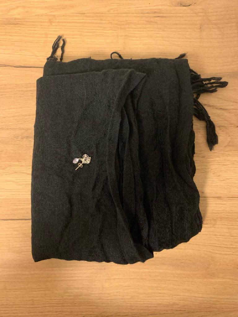 Das Bild zeigt einen Schal und ein paar Modeschmuck-Ohrringe
